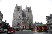 French firefighters gather at the scene of a blaze at the Cathedral of Sts. Peter and Paul in Nantes July 18, 2020. Police are investigating the incident as arson because the fire started in three different places. (CNS photo/Stephane Mahe, Reuters)