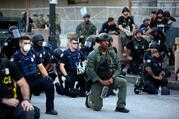 Police officers in Atlanta kneel with protesters on June 1, following a white police officer's killing of George Floyd, an African American, in Minneapolis on May 25. (CNS photo/Dustin Chambers, Reuters)