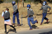 Zimbabwe riot police break up a protest for better pay and personal protective equipment by nurses in Harare in July. (AP photo/Tsvangirayi Mukwazhi)