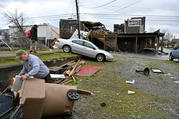 A man in Nashville, Tenn., picks up debris near his business March 3, 2020, after a tornado hit the area. In the Nashville Diocese, people and parishes, as well as Catholic Charities of Tennessee, are balancing their response to the coronavirus with ongoing tornado recovery. (CNS photo/Harrison McClary, Reuters