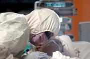 A medical worker in a protective suit treats a coronavirus patient in an intensive care unit at the Casalpalocco hospital in Rome March 24, 2020. (CNS photo/Guglielmo Mangiapane, Reuters)