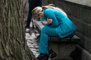 A health care worker in New York City rests on a bench near Central Park on March 30. (CNS photo/Jeenah Moon, Reuters)