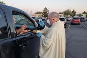 Bishop Peter Baldacchino of Las Cruces, N.M., wears a mask and gloves while giving Communion to a passenger of a vehicle during the Easter Vigil in the parking lot of the Cathedral of the Immaculate Heart of Mary in Las Cruces April 11, 2020. Bishop Baldacchino became the first-known U.S. prelate to lift a diocesan ban on public Mass April 15, 2020, and told priests they may resume sacramental ministry if they follow state health mandates. (CNS photo/courtesy David McNamara, Diocese of Las Cruces)