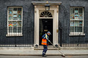 A street cleaner sweeps outside a residence in London May 4, 2020, during the COVID-19 pandemic. (CNS photo/John Sibley, Reuters)