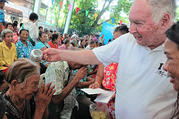 U.S. Redemptorist Father Joe Maier blesses a woman during Thai New Year festivities in 2018 at his Mercy Centre in Bangkok. The 80-year-old priest has been working in the slums of Bangkok for more than 40 years. (CNS photo/courtesy Tibor Krausz)