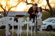 Meredith Cooper, of San Antonio, Tex., and her 8-year-old daughter, Heather, visit a memorial of 26 metal crosses near First Baptist Church in Sutherland Springs, Tex., on Nov. 6. (Jay Janner/Austin American-Statesman via AP)