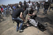An elderly Palestinian man falls on the ground after being shot by Israeli troops during a deadly protest at the Gaza Strip's border with Israel on May 14. Thousands of Palestinians are protesting near Gaza's border with Israel, as Israel celebrates the inauguration of a new U.S. Embassy in contested Jerusalem. (AP Photo/Khalil Hamra)