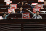 Pro-democracy lawmakers in Hong Kong react to the Legislative Council's passage on June 14 of a bill giving China jurisdiction over a train station connecting the city to the mainland's high-speed rail network. (AP Photo/Kin Cheung)