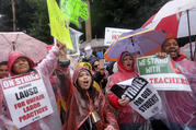 Teachers and supporters hold signs in the rain during a rally on Jan. 14 in Los Angeles. Thousands of Los Angeles teachers went on strike for the first time in three decades after contract negotiations failed in the nation's second-largest school district. (AP Photo/Ringo H.W. Chiu)