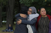 Mourners hug on March 18 after visiting the Masjid Al Noor mosque in Christchurch, New Zealand, the site of a terrorist attack last Friday. (AP Photo/Vincent Yu)