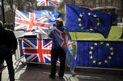 An anti-Brexit supporter stands by European and British Union flags placed opposite the Houses of Parliament in London, on March 18. (AP Photo/Matt Dunham)