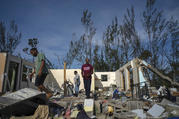 George Bolter, left, and his parents walk through the remains of his home destroyed by Hurricane Dorian in the Pine Bay neighborhood of Freeport, Bahamas, on Sept. 4. (AP Photo/Ramon Espinosa)