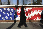 A mourner leaves a funeral ceremony for Iranian Gen. Qassim Soleimani and his comrades, passing graffiti on the wall of the former U.S. Embassy in Tehran, Iran, on Jan. 6. (AP Photo/Vahid Salemi)