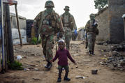 South African National Defense Forces patrol the Sjwetla informal settlement after pushing back residents into their homes on the outskirts of the Alexandra township in Johannesburg, on April 20. The residents were protesting the lack of food. (AP Photo/Jerome Delay)