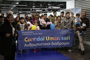 "Refugees sponsored by the Vatican and the Sant'Egidio Community hold a banner supporting ""Human Corridors"" upon their arrival at Fiumicino airport on Dec. 4. (AP Photo/Alessandra Tarantino)"
