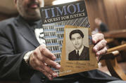 Imtiaz Cajee, nephew of Ahmed Timol, poses with his book about the activist on Aug. 24 in the North Gauteng High Court in Pretoria, South Africa. (AP Photo, File)