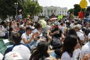 Demonstrators sit on the ground along Pennsylvania Ave. in front of the White House in Washington, on Saturday, April 29, 2017, during a demonstration and march. (AP Photo/Pablo Martinez Monsivais)