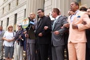 Local elected and religious leaders link arms in prayer, led by Father Eric Cruz, regional director of Catholic Charities Bronx, on the steps of the Bronx County Building in New York on June 22. (Photo: Allyson Escobar)