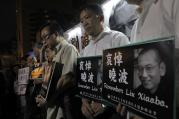 Protesters mourn jailed Chinese Nobel Peace laureate Liu Xiaobo during a demonstration outside the Chinese liaison office in Hong Kong on July 13. Officials say China's most prominent political prisoner, Nobel Peace Prize laureate Liu Xiaobo, has died. He was 61. (AP Photo/Vincent Yu)