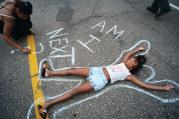 In this July 7, 2016 photo, Tia Williams and her daughter Aissa create a display on the street outside the Minnesota governor's official residence in St. Paul, Minn., as people gathered to protest the shooting death of Philando Castile by police (Richard Tsong-Taatarii/Star Tribune via AP)/Star Tribune via AP).