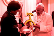 Bolivian President Evo Morales presents a gift to Pope Francis at the government palace in La Paz, Bolivia, July 8. The gift was a wooden hammer and sickle -- the symbol of communism -- with a figure of the crucified Christ. (CNS photo/L'Osservatore Romano/Illustration: America Media)