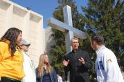 TRUE DIALOGUE. The Rev. Philip Lowe, chaplain of Neumann University in Aston, Pa., with students outside the campus chapel.