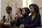 A family prays after arriving for Sunday Mass in 2011 at St. Joseph's Catholic Church in Alexandria, Va.