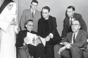 "The Rev. Andrew M. Greeley, seated left, talks with fellow speakers following a symposium on ""New Horizons in Catholic Thought"" in 1962."