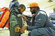 HELPING HAND. Denver Broncos defensive end Robert Ayers helps a boy at the Knights of Columbus Coats for Kids event in Jersey City, N.J., in 2014.