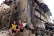 Their City in Ruins: Children sit among rubble in a besieged neighborhood in Homs, Syria, on Sept. 19