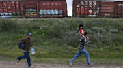 A Salvadoran father carries his son while running in Huehuetoca, Mexico, in June 2015 as they try to board a train heading to the U.S-Mexico border. (CNS photo/Edgard Garrido, Reuters)