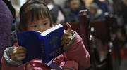 A girl reads a Bible during Mass in the state-approved Xuanwumen Catholic Church in Bejing, China, in December 2016. (CNS photo/How Hwee Young, EPA)