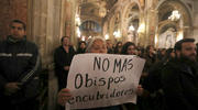 A woman holds a sign in protest while praying as Cardinal Ricardo Ezzati of Santiago, Chile, celebrates Mass on July 25 at the cathedral in Santiago. The Chilean prosecutor's office has issued a subpoena to Cardinal Ezzati regarding his role in the alleged cover-up of sexual abuse by clergy members. (CNS photo/Ivan Alvarado, Reuters)