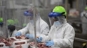 Workers inside a Sioux Falls, South Dakota, pork processing plant wear protective gear and are separated by plastic partitions as they carve up meat. (Photo courtesy Smithfield Foods via AP)