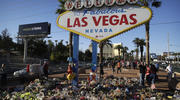 Flowers, candles and other items surround the famous Las Vegas sign at a makeshift memorial for victims of a mass shooting (AP Photo/John Locher).