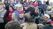 "On Jan. 18, a teenager wearing a ""Make America Great Again"" hat, center left, stands in front of an elderly Native American singing and playing a drum in Washington. (Survival Media Agency via AP)"