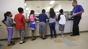 Detained immigrant children line up in the cafeteria in this Sept. 10, 2014 file photo at the Karnes County Residential Center, a detention center for immigrant families operated by the GEO Group in Karnes City, Texas. (AP Photo/Eric Gay, File)