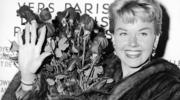 In this April 15, 1955, file photo, American actress and singer Doris Day holds a bouquet of roses at Le Bourget Airport in Paris after flying in from London. (AP Photo, File)