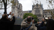 People take photos of the Notre Dame Cathedral in Paris, one day after a major blaze broke out at Paris' iconic cathedral. (AP Photo/Michel Euler, FILE)