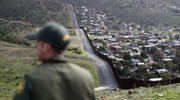 In this Feb. 5, 2019, file photo, Border Patrol agent Vincent Pirro looks on near a border wall that separates the cities of Tijuana, Mexico, and San Diego, in San Diego. (AP Photo/Gregory Bull, File)