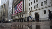 A pedestrian walks past the New York Stock Exchange on March 19. (AP Photo/Kevin Hagen)