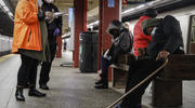 Homeless outreach personnel assist passengers found sleeping on subway cars in New York City on April 30. New York has the highest income inequality among the 50 states, comparable to the inequality in the nation of Angola. (AP Photo/John Minchillo, File)