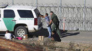 In this Dec. 15, 2018, file photo, Honduran asylum seekers are taken into custody by U.S. Border Patrol agents in San Diego. (AP Photo/Moises Castillo, File)