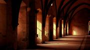 A dim corridor lined with heavy arches
