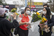 Roula AbiSamra, center, and Chelsey, right, prepare to lay flowers bouquets at a makeshift memorial outside of the Gold Spa in Atlanta, one of the sites of a shooting spree that killed eight people in the Atlanta area this Tuesday. (Alyssa Pointer/Atlanta Journal-Constitution via AP, File)