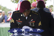 Sgt. Donald Young places a U.S. flag over the casket of Sgt. La David Johnson during his burial service in Hollywood, Fla., on Saturday, Oct. 21, 2017. Mourners remembered not only a U.S. soldier whose combat death in Africa led to a political fight between President Donald Trump and a Florida congresswoman but his three comrades who died with him. (Matias J. Ocner/Miami Herald via AP)