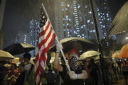 A protester waves a U.S. flag as hundreds of protesters gather outside Kwai Chung police station in Hong Kong on July 30. Protesters clashed with police again in Hong Kong on Tuesday night after reports that some of their detained colleagues would be charged with the relatively serious charge of rioting. (AP Photo/Vincent Yu)