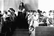 Students from Fort Albany Residential School reading in class overseen by a nun, circa 1945. From the Edmund Metatawabin collection at the University of Algoma. (Wikimedia Commons)