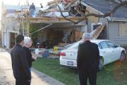 GOOD SHEPHERDS. Rev. Johnson Lopez, left, and Bishop David J. Malloy visit a home in Illinois damaged by a tornado last April.