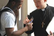 Michael Zhang, a seminarian, talks with a young man in New York.